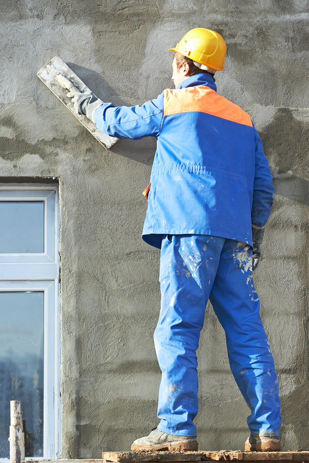 Male builder plastering exterior wall during industrial facade b